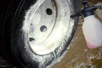 Reiniger wird mittels Schaumsprüher auf eine Felge aufgetragen