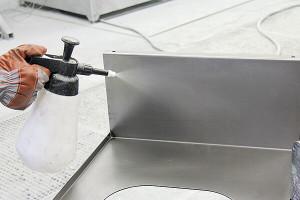 Reiniger wird auf ein Metallteil aufgesprüht