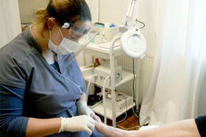 Fußpflegerin mit Schutzkleidung